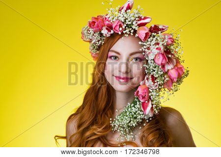 eyed redhead girl with bright makeup and a wreath of spring flowers tulips on the head on yellow background.