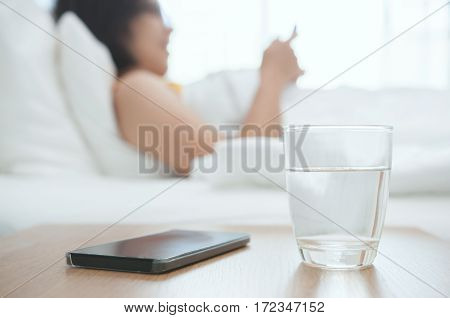 Close up Woman glass of water with smartphone on foreground. Beautiful Asian girl reading her book and lying on bed.