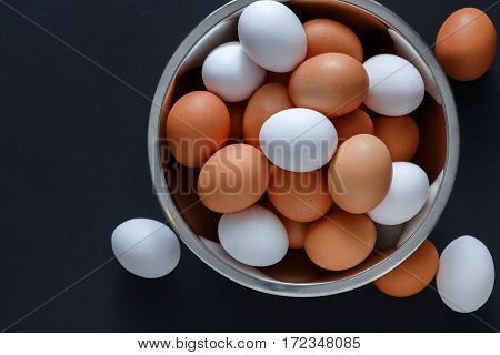 Fresh brown and white eggs in steel bowl isolated at black background with copy space. Top view. Natural healthy organic food, cooking concept