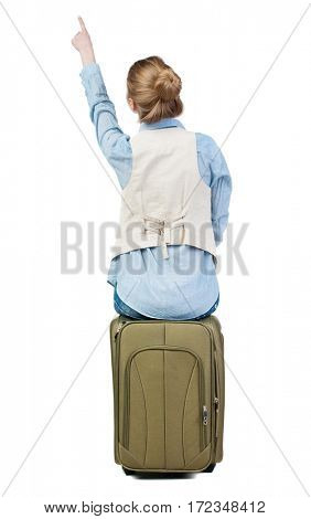back view of woman sits on a suitcase and pointing.  backside view of person.  Rear view people collection. Isolated over white background.