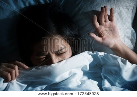 Nightmare concept. Dark tone. Asian women having trouble about getting up early in the morning. Girl hate sound from alarm clocks.