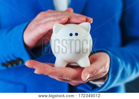 Woman cuddles piggy coin bank responsible home budgeting and money saving