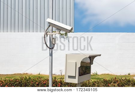 CCTV or surveillance camera recording important events and a guard house and property with the sunrise in the morning at the big city background.