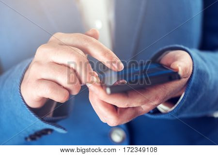Female hands with mobile phone finger on touchscreen