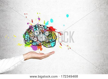 Close up of man hand in a black suit holding a hovering colorful brain and gears sketch drawn on a concrete wall. Concept of creativity