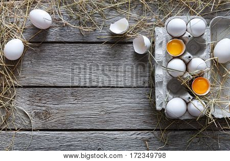 Fresh chicken eggs background. White eggs in craft carton pack on hay at rustic wood table with copy space. Top view. Natural healthy food and organic farming concept.