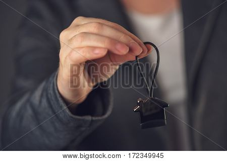 Female real estate agent with house model key ring selective focus