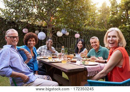 Portrait Of Mature Friends Enjoying Outdoor Meal In Backyard