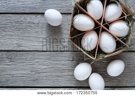 Fresh chicken eggs background. White eggs in craft carton pack on hay at rustic wood table. Top view with copy space. Rural still life, natural healthy food and organic farming concept.