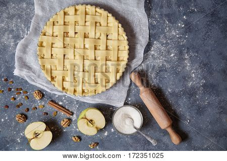 Apple pie tart homemade American traditional autumn sweet pastry baked food cooking recipe with ingridients, rolling pin, egg yolk, sugar flat lay on blue vintage background, top view