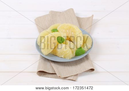 plate of peeled and sliced pomelo on beige place mat