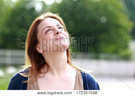 outdoor portrait of adult happy woman looking in the skies