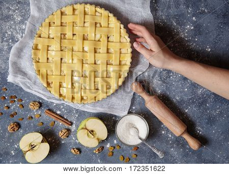 Apple pie tart homemade traditional autumn sweet pastry baked food woman cooking recipe with ingridients, rolling pin, egg yolk, sugar flat lay on blue vintage background, top view