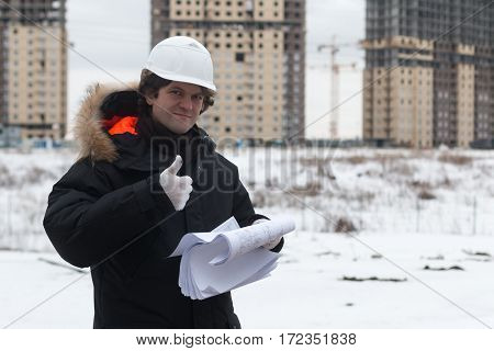 Engineer standing on the background of a new apartment building. House is built. Engineer in a helmet with papers in hand. The concept of new housing construction, real estate.