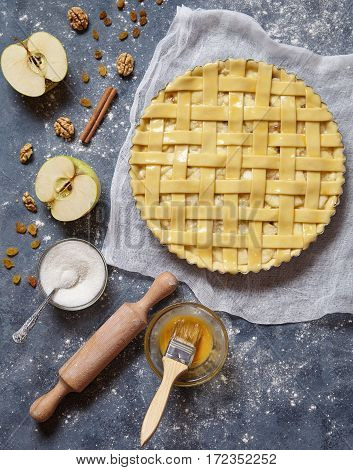Apple pie tart raw sweet pastry baked food woman cooking recipe with ingridients, rolling pin, egg yolk, sugar flat lay on blue vintage background, top view