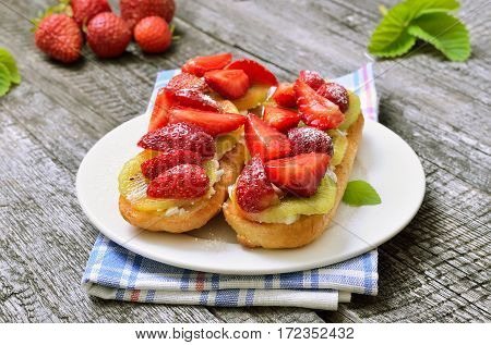 Bruschetta with strawberries and kiwi on white plate