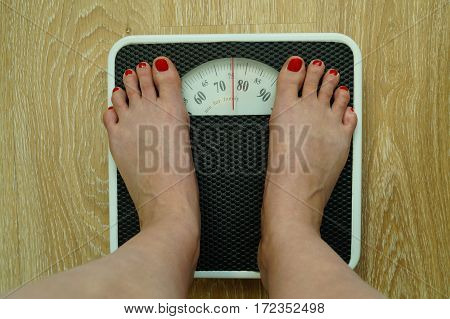 girls feet standing on floor scales in the room