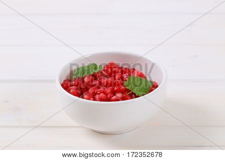 bowl of pomegranate seeds on white background