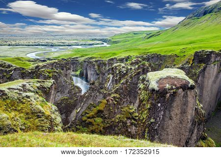 The concept of active northern tourism. Vertical huge rocks surround the stream with glacial water. The striking canyon in Iceland. The Icelandic tundra in July