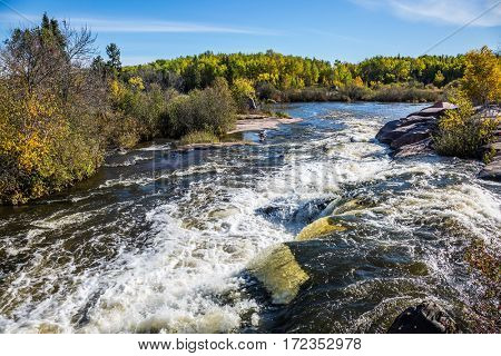 Old Pinava Dam. Foam water rapids on the smooth stones of the Winnipeg River. The concept of ecological and adventure tourism