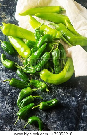 Green, fresh jalapeno peppers. Spicy Mexican food. Dark background