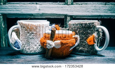Two big and one small tea mugs wearing wool sweaters. Concept of family teatime