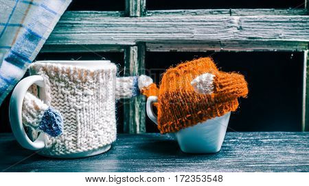 Mug in white sweater attiring small teacup with red sweater