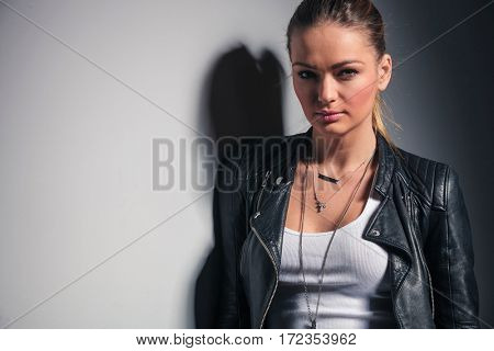 smiling blonde woman in leather jacket standing near grey wall in studio