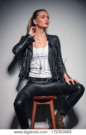 side view picture of a young woman in leather clothes with one hand behind her neck and looks away