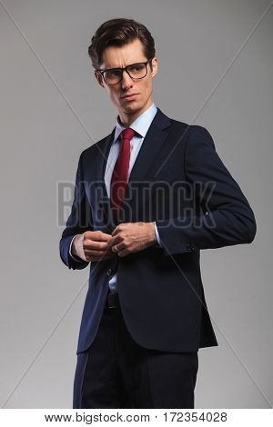 portrait of a young business man buttoning his suit and looks to side in studio on grey background
