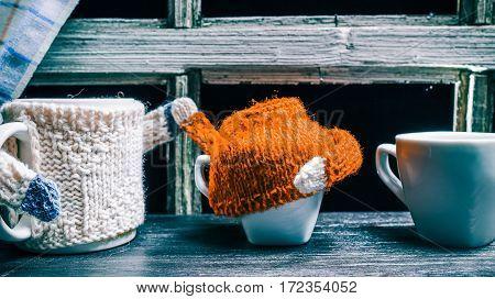 Big mug in white sweater attiring small tea cups
