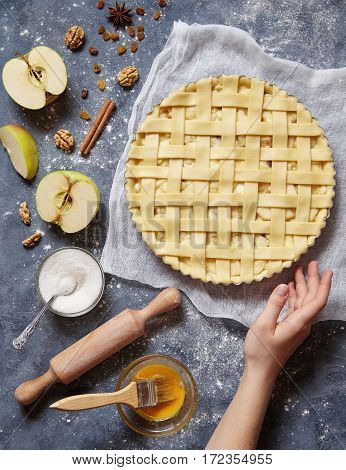 Apple pie tart raw homemade sweet pastry baked food recipe with ingridients, rolling pin, egg yolk, sugar flat lay on blue vintage background, top view
