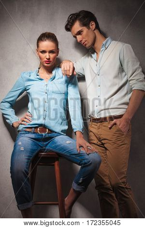 woman sitting on stool while boyfriend leans on her shoulder , studio picture