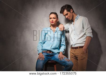 laughing young casual man leans on his girlfriend while she sits on a stool in studio