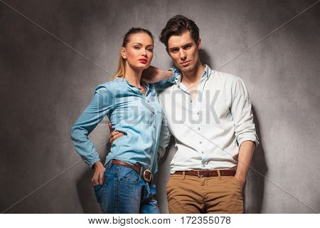 casual woman leaning on her boyfriend and looks at the camera, studio picture