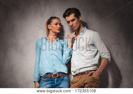 woman is holding her finger on casual man's chin , studio picture