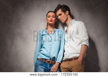 young casual couple standing close to each other in studio, leaning on wall
