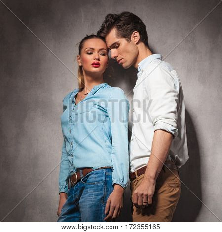 young casual couple is in love, standing together in studio