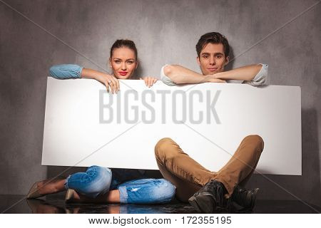 smiling young couple is sitting and holding blank board is studio