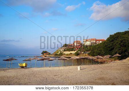 Nesebar Bulgaria - September 05 2014: Pebble beach thatched umbrellas and a rescue boat. Seaside resort and ancient old town Nesebar in Bulgaria. Bulgarian Black Sea Coast.