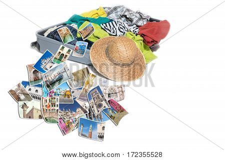 Studio shot of a suitcase with scattered clothing and straw hat. Photos of Venice landmarks are lying in front of the suitcase. Everything is on a white background.