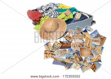 Studio shot of a suitcase with scattered clothing and straw hat. Photos of Egypt landmarks are lying in front of the suitcase. Everything is on a white background.