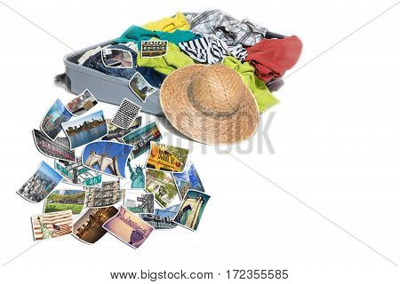Studio shot of a suitcase with scattered clothing and straw hat. Photos of New York City landmarks are lying in front of the suitcase. Everything is on a white background.