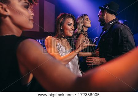 Young men and women having fun at disco club. Group of young friends dancing in night club.