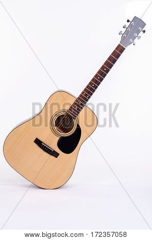 acoustic guitar stands diagonally on a white background isolated