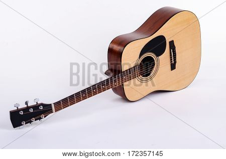 acoustic guitar lying flat on a white background isolated