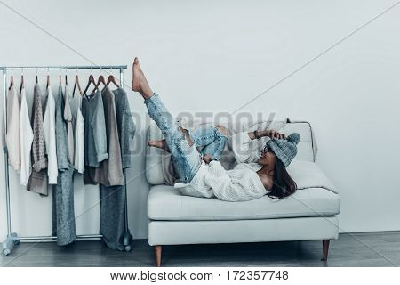Having fun at home. Playful young woman in casual wear and knit hat touching her head with hand and putting feet up while lying on sofa at home near her clothes hanging on the racks