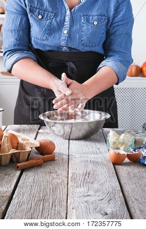 Baking concept. Flour, milk, butter, yeast, spices and eggs carton on rustic wood table, many ingredients. Cropped image of unrecognizable woman stir dough. Female baker at cooking classes, copy space