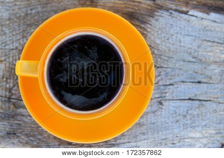 Cup of coffee on the wooden table. Top view
