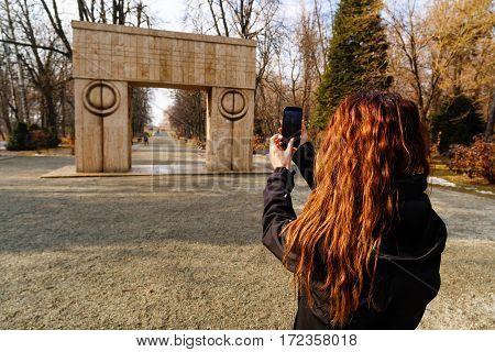 woman tourist traveling through Romania. Targu Jiu kissing gate